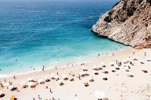 Pláž s bielym pieskom, tyrkysovým morom a mnohými dovolenkujúcimi