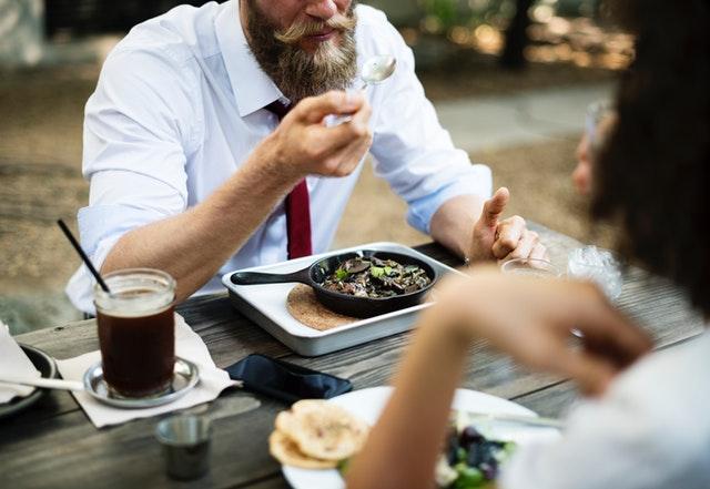Muž sediaci pri stole pred tanierom s jedlom