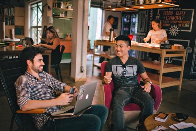 Dvaja muži, ktorí diskutujú pri notebooku v kaviarni.jpg
