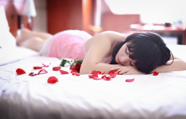 Žena v ružovej erotickej košieľke leží na posteli.jpg