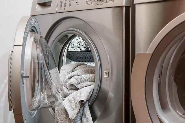Práčka, z ktorej trčia béžové uteráky