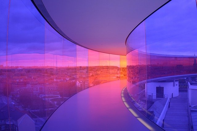 Moderná budova s chodbou s presklenými stenami vo fialových farbách.jpg