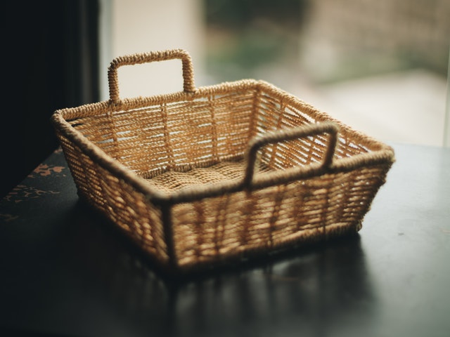 Prázdny prútený košík položený na stole