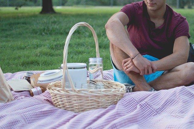Muž sedí na deke vedľa prúteného košíka s jedlom