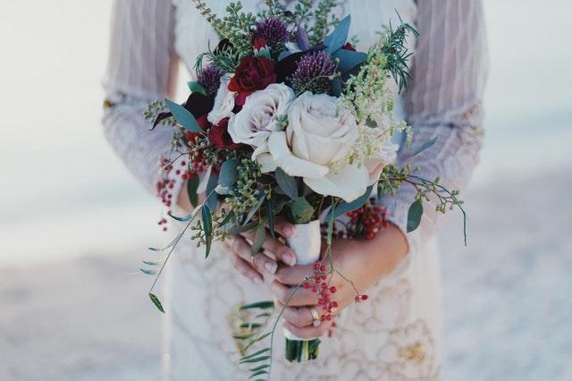 Žena v svadobných šatách drží pred sebou farebnú kyticu z kvetov.jpg