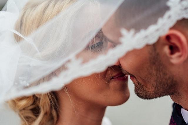 Muž a žena sa bozkávajú pod bielym závojom.jpg