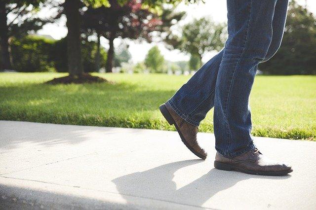 Muž v rifliach kráča po chodníku.jpg