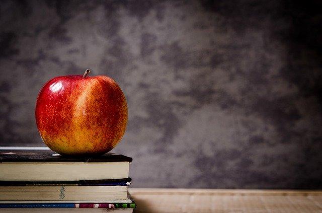 Červené jablko položené na knihách